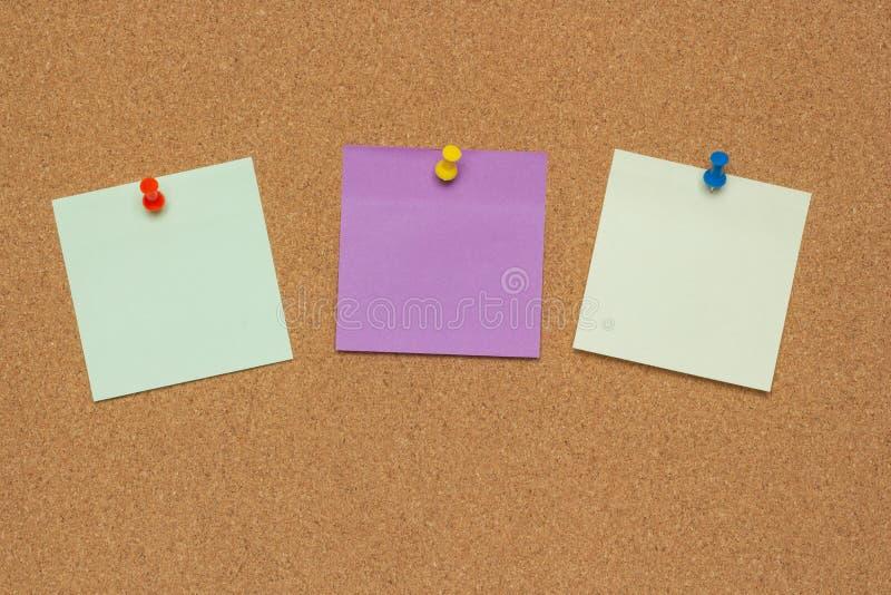 Tre färgrika klibbiga anmärkningar med häftstift och tomt utrymme som isoleras på korkbakgrund, skolabegrepp arkivfoto