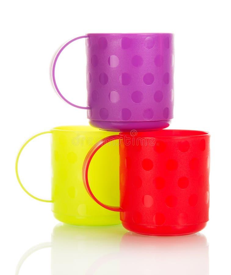 Tre färgrika plast-koppar som isoleras på vit fotografering för bildbyråer