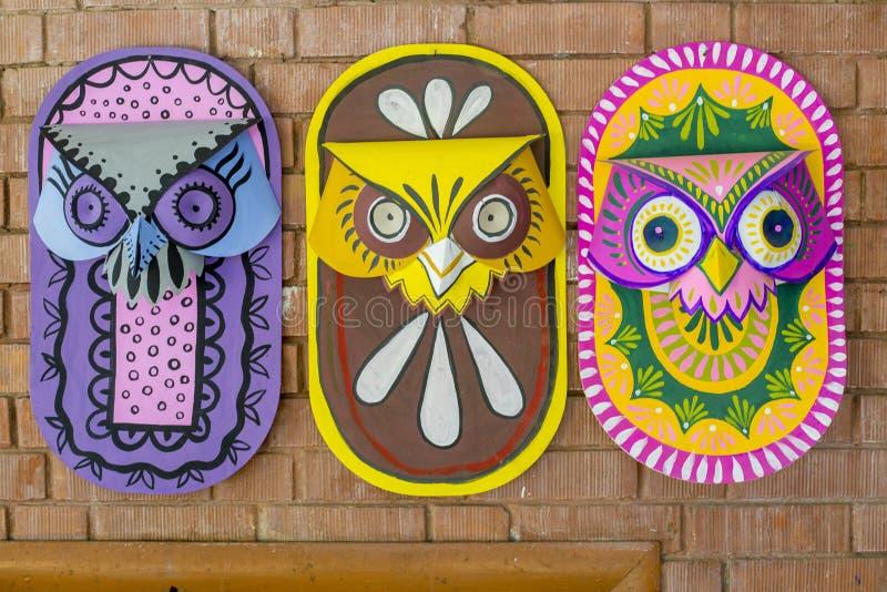 Tre färgrika ugglamaskeringar som hänger på konst, instiftar väggen royaltyfria foton