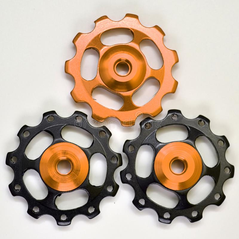 Tre färgrullar, svarta guld- kugghjul för bakre derailleur för cykel på en vit bakgrund arkivfoton