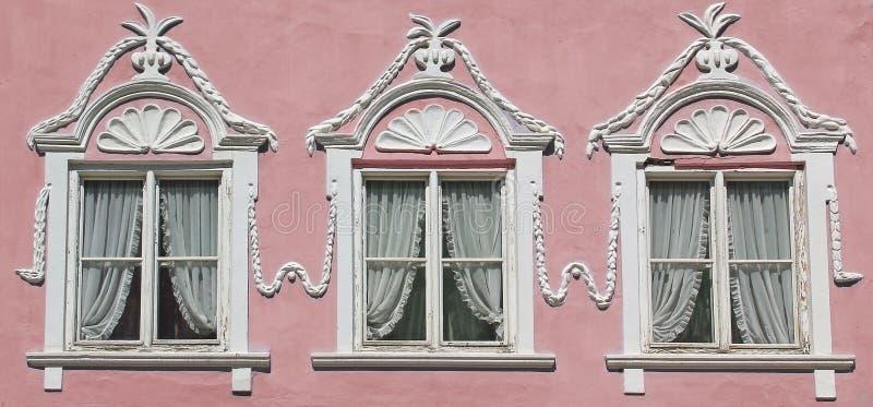 Tre fönster på rosa färger inhyser väggen med den utsmyckade stuckaturen royaltyfri fotografi