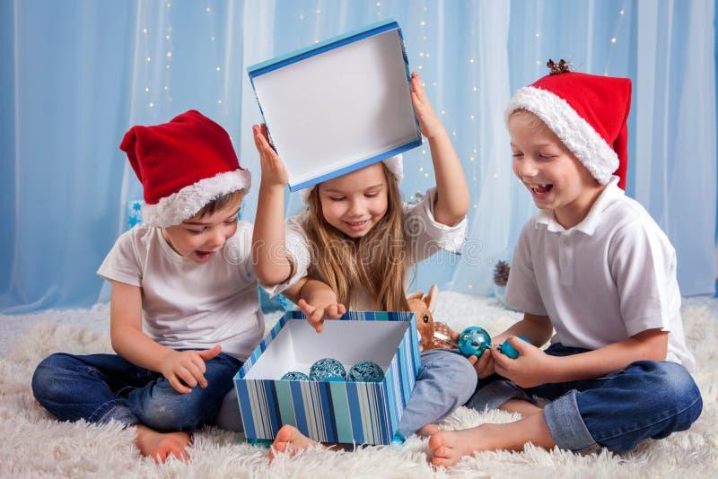 Tre förtjusande ungar, förskole- barn, syskon och att ha gyckel fo arkivbild