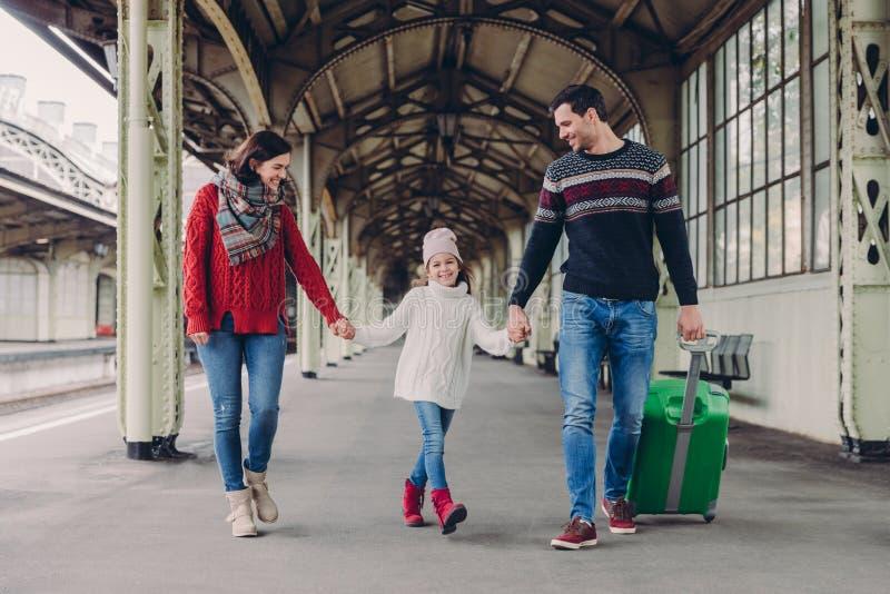 Tre familjemedlemmar på järnvägsstation Den lyckliga modern, dottern och fadern har positiva ansiktsuttryck, väntar på på drevet royaltyfri fotografi