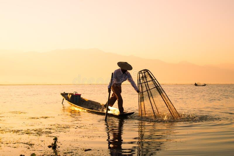 Tre fermi dei pescatori pescano per alimento nell'alba nel lago Inle fotografia stock