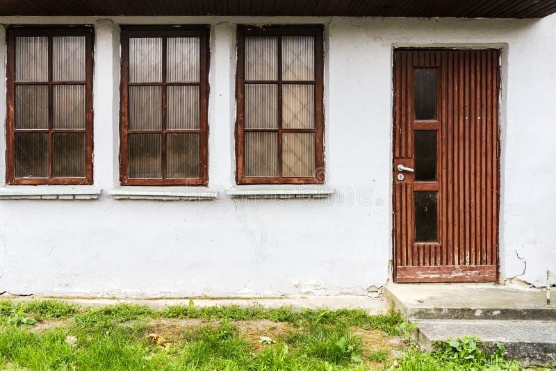 Tre finestre e una porta fotografia stock