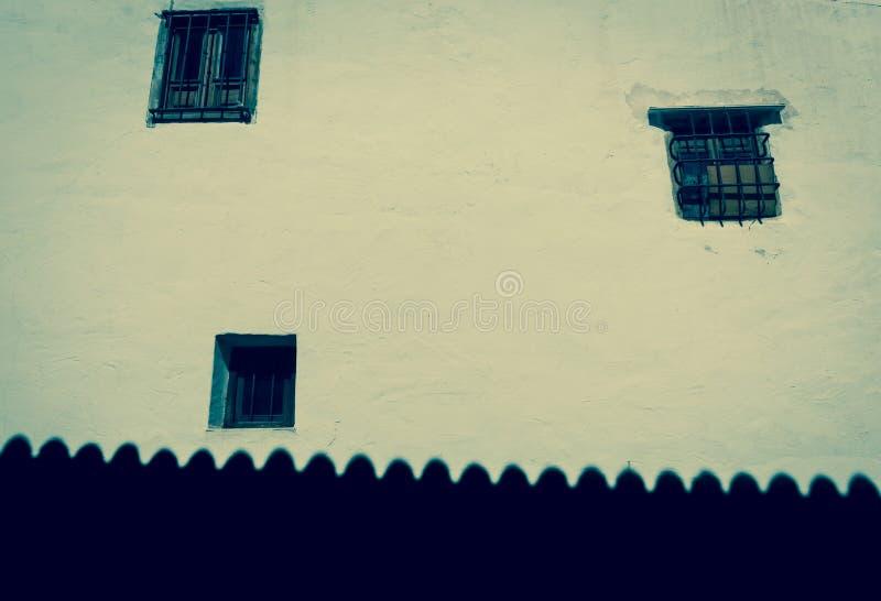 Tre finestre nell'ombra bianca del tetto e della parete lungo la base fotografia stock