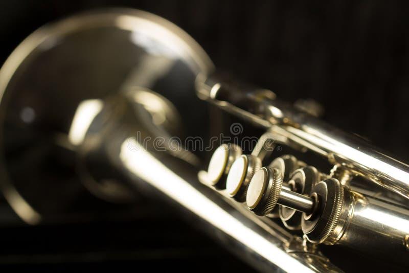Tre fingerknappar tätt upp av trumpet med klockan och trimmaglidbanan royaltyfria foton