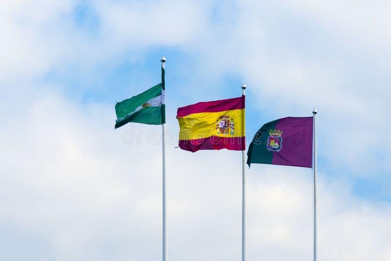 Tre flaggor: Spanien, Andolusia och Malaga mot den blåa himlen med vita moln royaltyfri foto