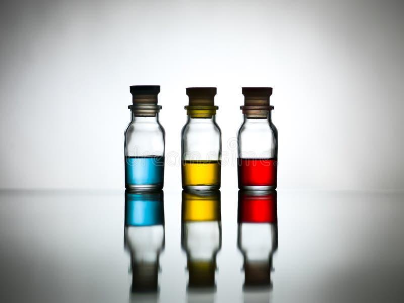 Tre flaskor med den kulöra lösningen på tabellen arkivfoto