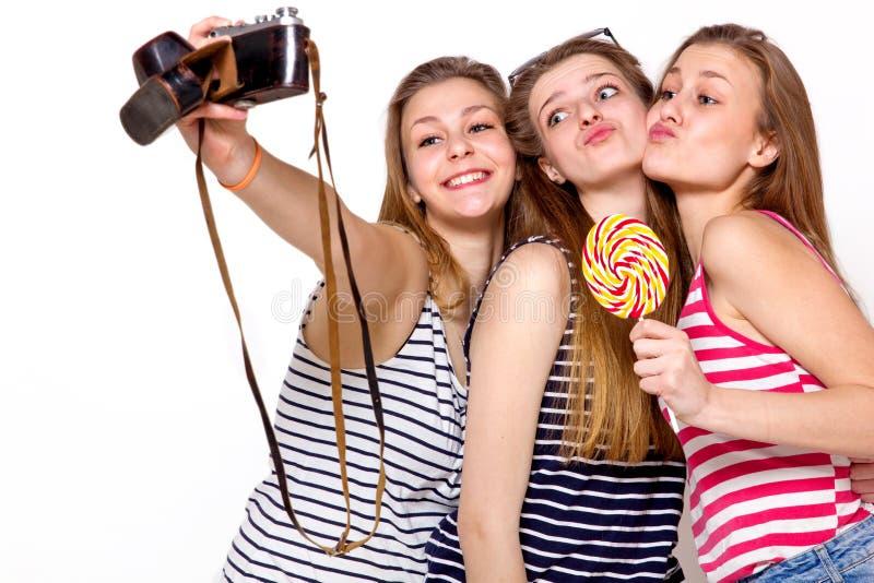 Tre flickor har gyckel med kameran arkivbild