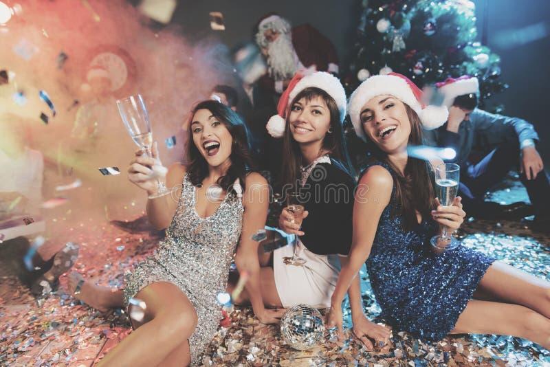 Tre flickor i härliga aftonklänningar sitter på golvet med exponeringsglas av champagne i deras händer arkivbilder