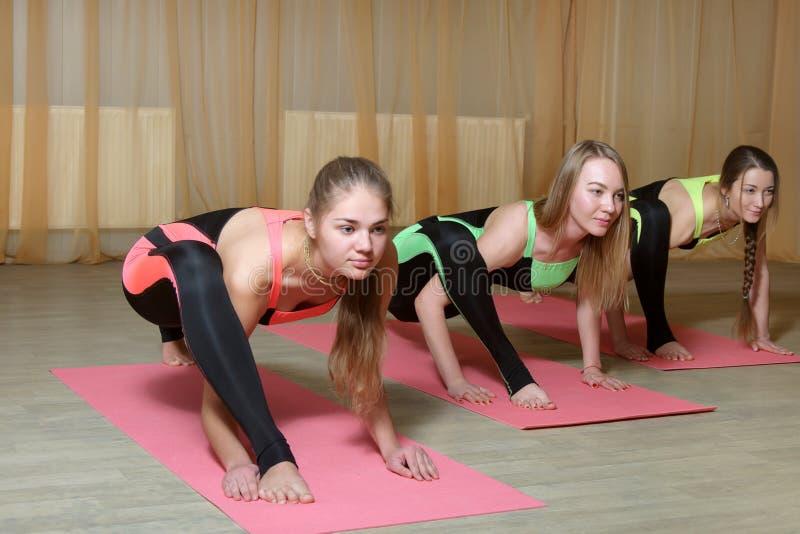 Tre flickor i identiska dräkter utför övningar arkivbild