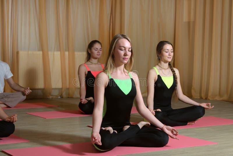 Tre flickor i identiska dräkter utför meditation arkivbilder