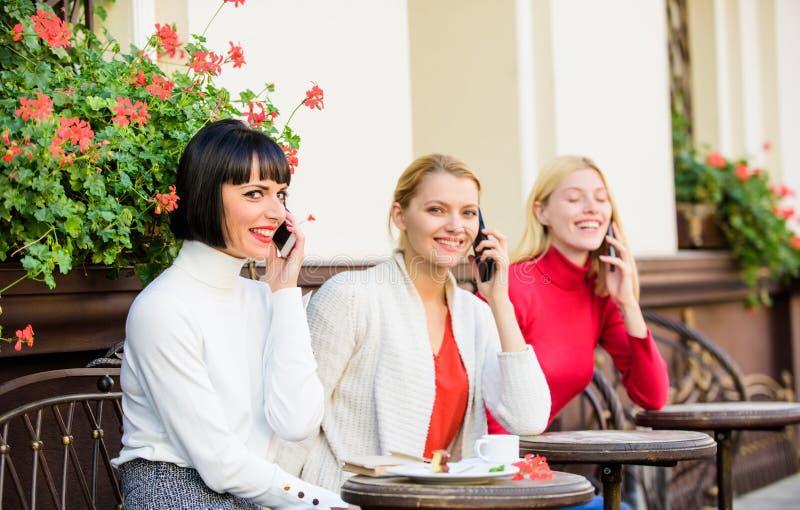 Tre flickor i kafét som talar på telefonen Konferenssamtal affärsmöte på lunch Folkanslutning modernt samh?lle arkivfoto