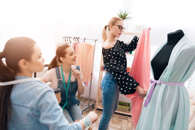 Tre flickor på plaggfabriken De diskuterar design av den nya klänningen fotografering för bildbyråer