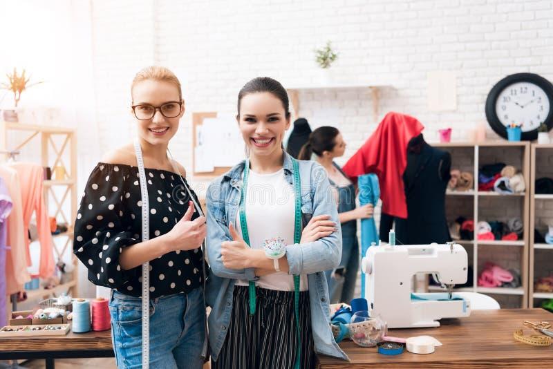 Tre flickor på plaggfabriken De ger tummar upp den färdiga nya klänningen royaltyfria bilder