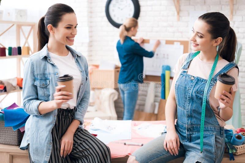 Tre flickor på plaggfabriken Två av dem dricker kaffe som talar och ler arkivbild