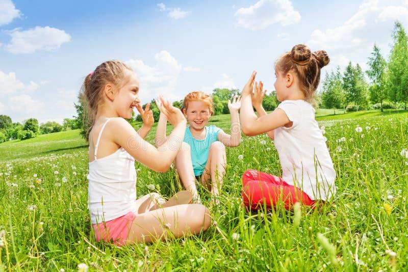 Tre flickor sitter på en underbar äng fotografering för bildbyråer