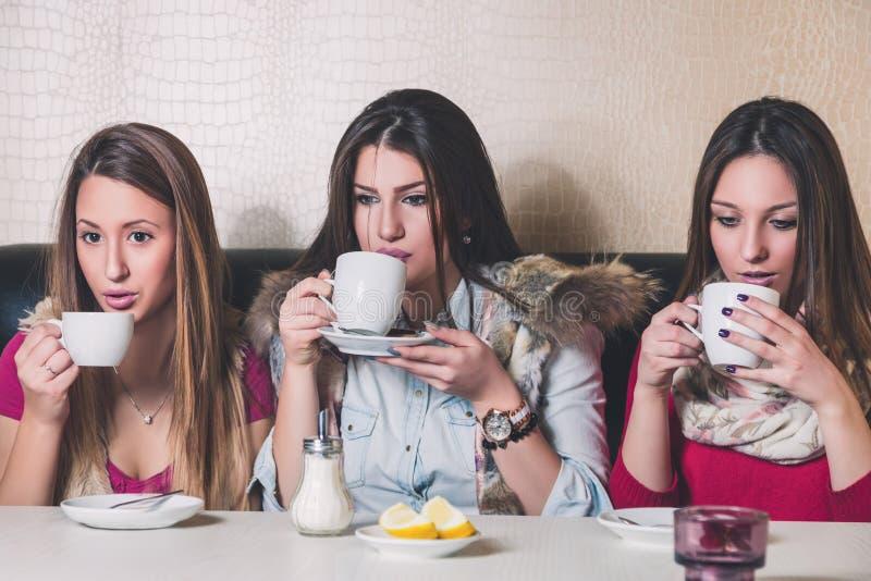 Tre flickor som dricker den varma drycken royaltyfri bild
