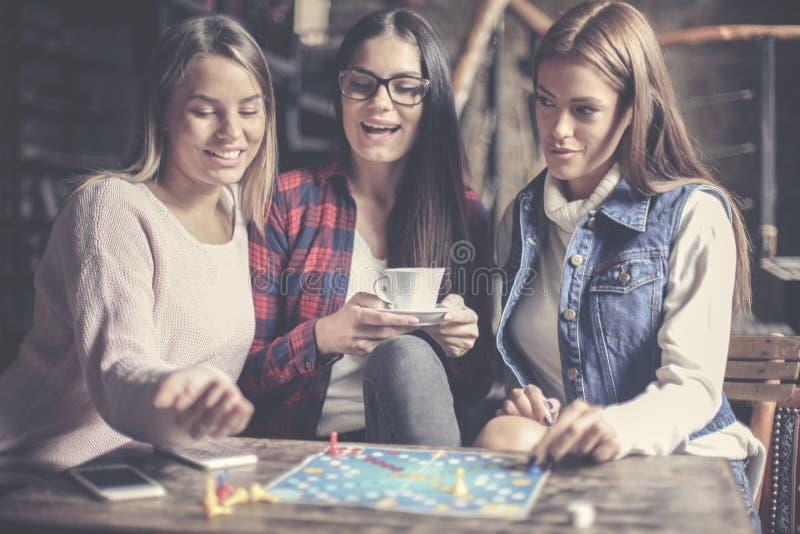 Tre flickor som har roligt och spelar leken arkivfoton