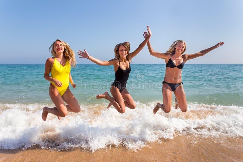 Tre flickor som hoppar på stranden nära havet royaltyfri fotografi