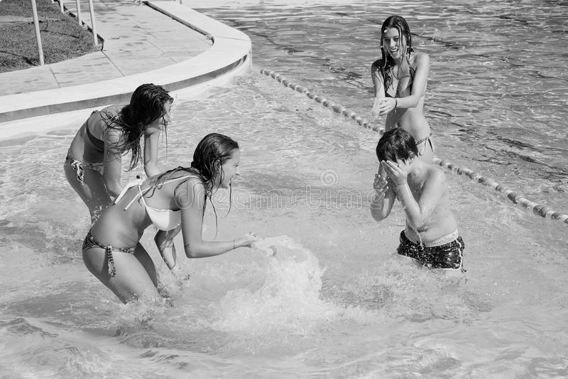 Tre flickor som plaskar pojken med vattenvapen i den svartvita pölen arkivbild