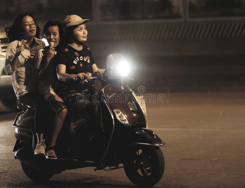 Tre flickor som rider på en motorisk sparkcykel royaltyfri fotografi