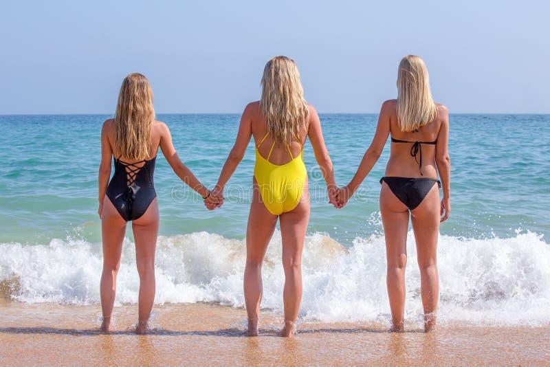 Tre flickor som rymmer händer på den soliga stranden arkivbilder