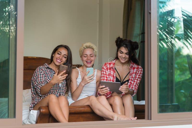 Tre flickor som sitter på Smart för sängbrukscell telefoner och den lyckliga le unga kvinnan för minnestavladator som direktanslu royaltyfri foto