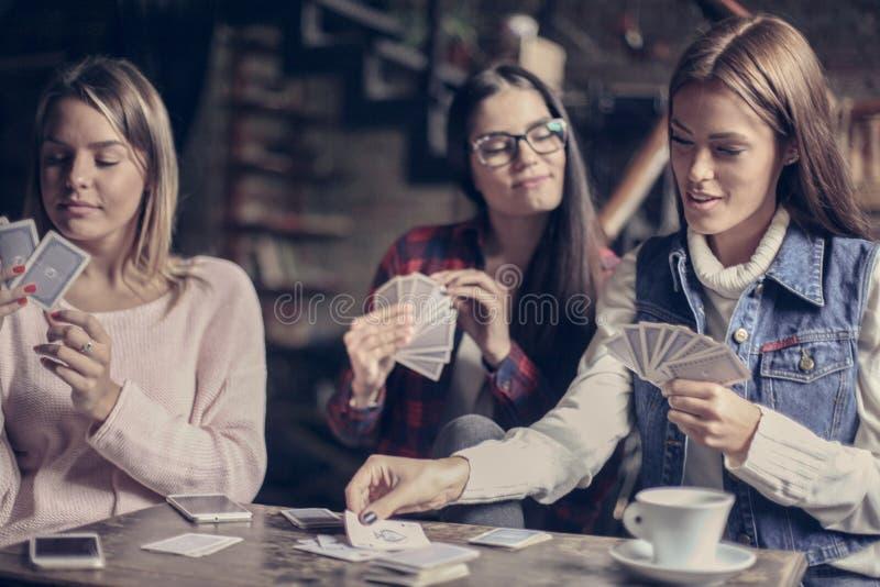 Tre flickor som spelar kortet i kafé royaltyfri fotografi