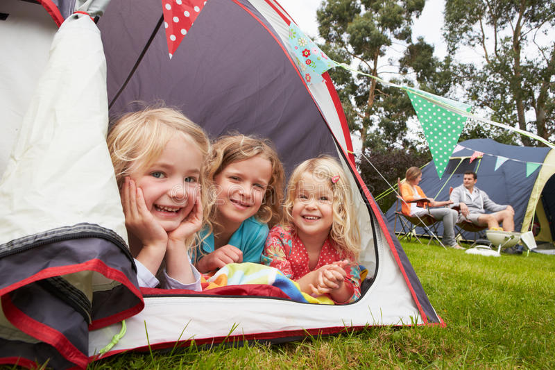 Tre flickor som tycker om campa ferie på campingplats royaltyfri foto