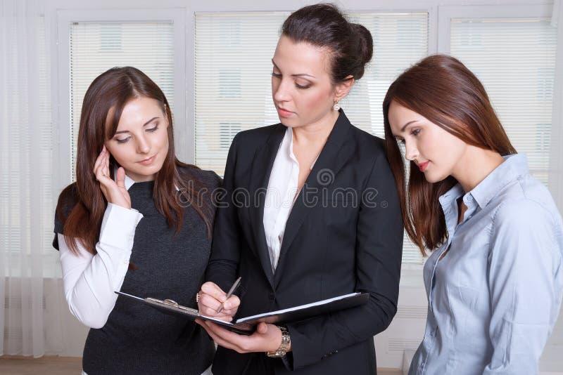 Tre flickor studerar informationen i en mapp royaltyfria foton