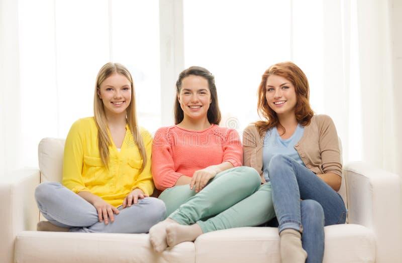 Tre flickvänner som har ett samtal hemma royaltyfria bilder