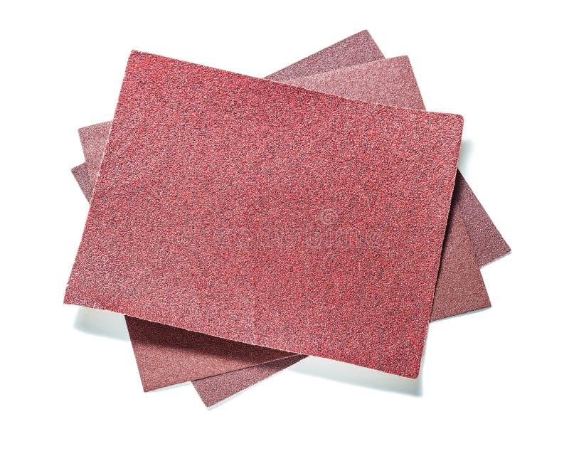 Tre fogli rossi di carta abrasiva isolati su bianco fotografia stock