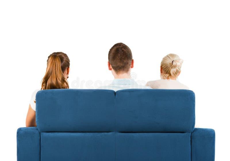 Tre folk sammanträde på en sofabaksida fotografering för bildbyråer