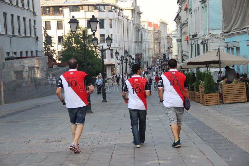Tre fotbollsfan i t-skjortor med inskriften Egypten och numret tio royaltyfri foto