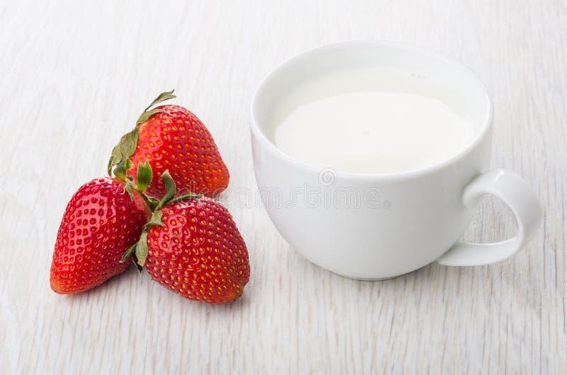 Tre fragole e tazze mature di latte sulla tavola immagini stock