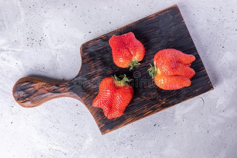 Tre fula mogna röda jordgubbar på bränd kökskärbräda på grå konkret bakgrund arkivfoto