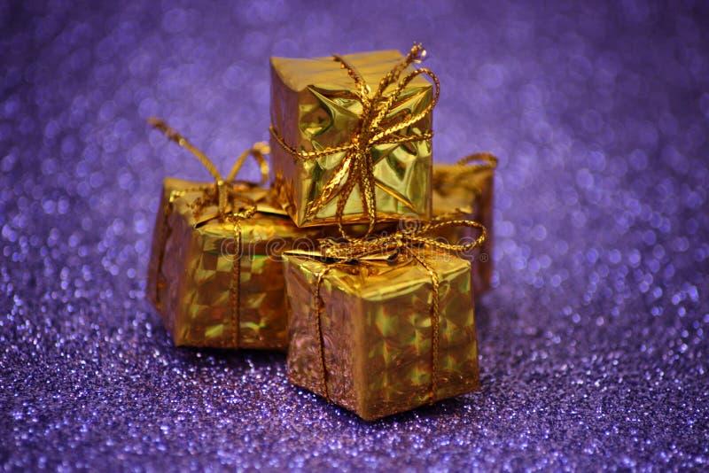 Tre gåvor i guld- emballage och en pilbåge på en briljant lila bakgrund med blurriness royaltyfri foto