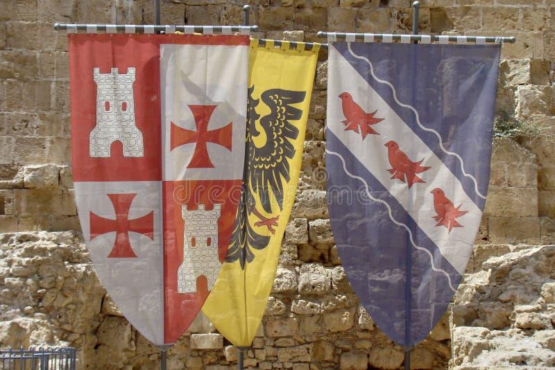 Tre gamla korsfarareflaggor och vapensköld royaltyfria foton