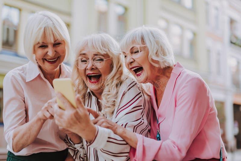 Tre gamla kvinnlig som ser telefonen och skratta royaltyfri fotografi