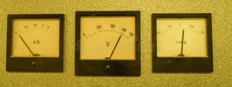 Tre gamla parallella instrument - meter för maktfaktor, voltmeter och amperemeter som isoleras på grå bakgrund royaltyfria bilder