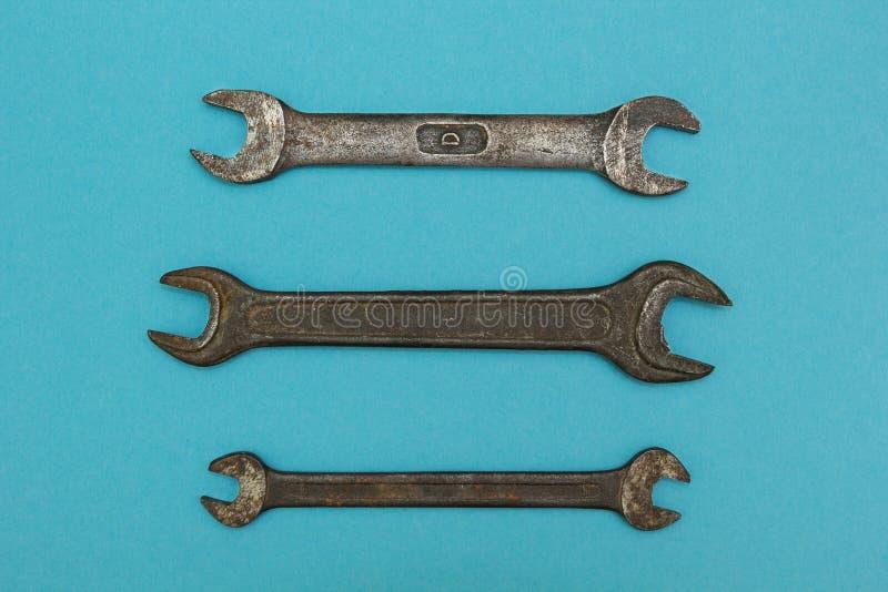 Tre gamla skiftnycklar på en blå bakgrund arkivbild