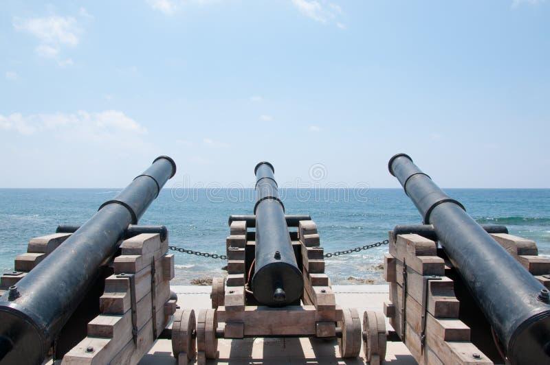 Tre gamla vapen för kanonboll på havskusten royaltyfri fotografi