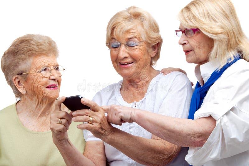 Tre gammalare kvinnor med mobiltelefon. royaltyfri foto