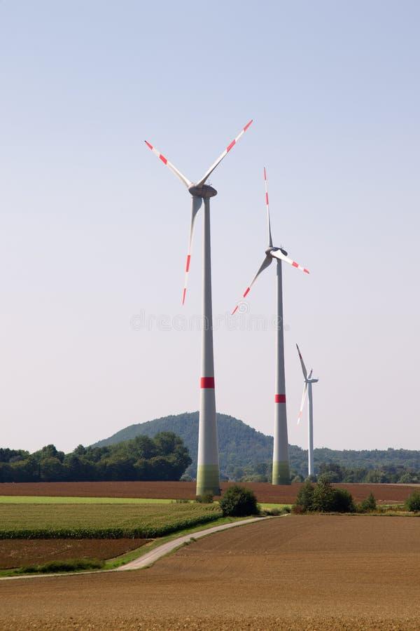 Tre generatori eolici in un paesaggio collinoso fotografia stock