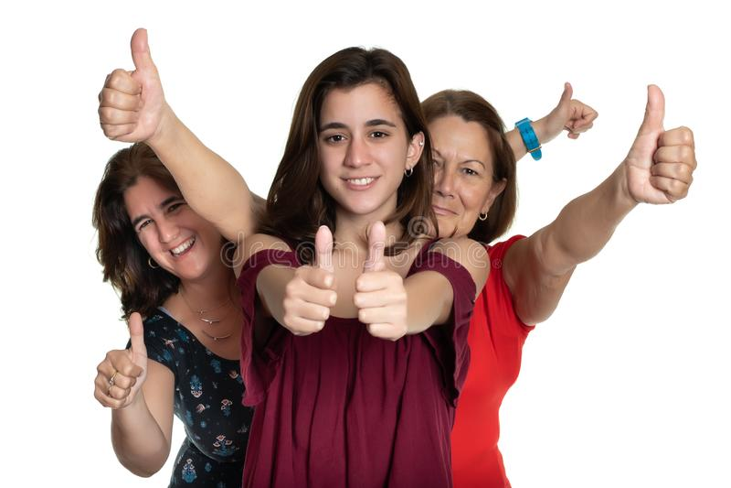 Tre generazioni di donne latine che sorridono e che fanno i pollici sul segno - su un fondo bianco immagine stock