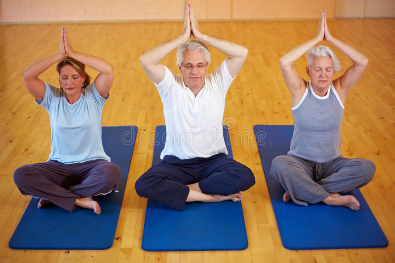 Tre genti che fanno yoga fotografia stock libera da diritti