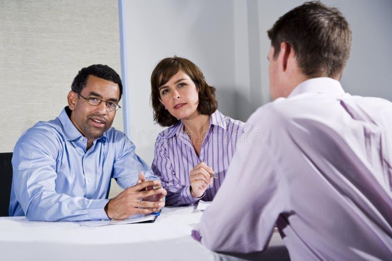 Tre genti dell'metà di-adulto che si siedono alla riunione della tabella immagini stock libere da diritti