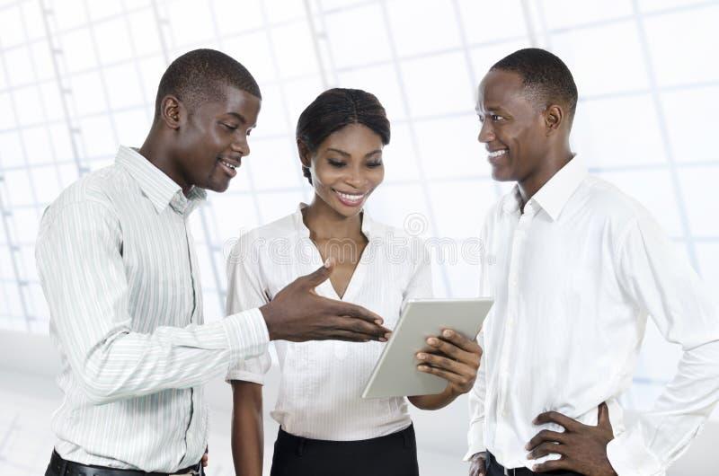 Tre genti di affari africane con il PC della compressa fotografia stock libera da diritti